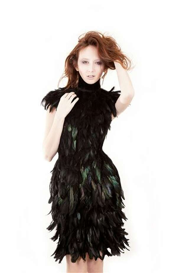 "This undated image released by Christian Fashion Week shows a model wearing a black feather dress designed by Julia Chew. Chew, 18, who recently graduated after being homeschooled by her parents, said her collection was inspired by nature. She's also been ""obsessed"" with feathers recently and crafted a stunning above-the-knee length dress entirely of dyed black feathers. Christian Fashion Week will kick off Friday and Saturday, Feb. 8-9 in Tampa, Fla. (AP Photo/Christian Fashion Week) Photo: HOEP / Christian Fashion Week"
