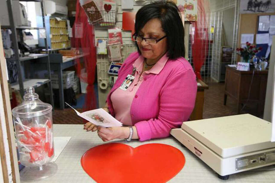 U.S. Postmaster Maria Carrasco reads a Thank You card sent to her at the Valentine, Texas post office, Tuesday, Feb. 7, 2012. The West Texas post office handles over 10 times more daily volume during the days leading up to Valentine's Day on February 14th. It's also on the list for possible closure by the U.S. Postal Service. Carrasco figured that she has hand-stamped Valentine cards destined for cities all over the world. Photo: Jerry Lara | San Antonio Express-News