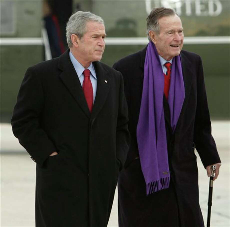 FILE - In this Dec. 26, 2008 file photo, President George W. Bush walks with his father, former President George H.W. Bush, at Andrews Air Force Base, Md. A criminal investigation is under way after a hacker apparently accessed private photos and emails sent between members of the Bush family, including both former presidents, according to reports Friday, Feb. 8, 2013. (AP Photo/Evan Vucci, File) Photo: Evan Vucci / AP