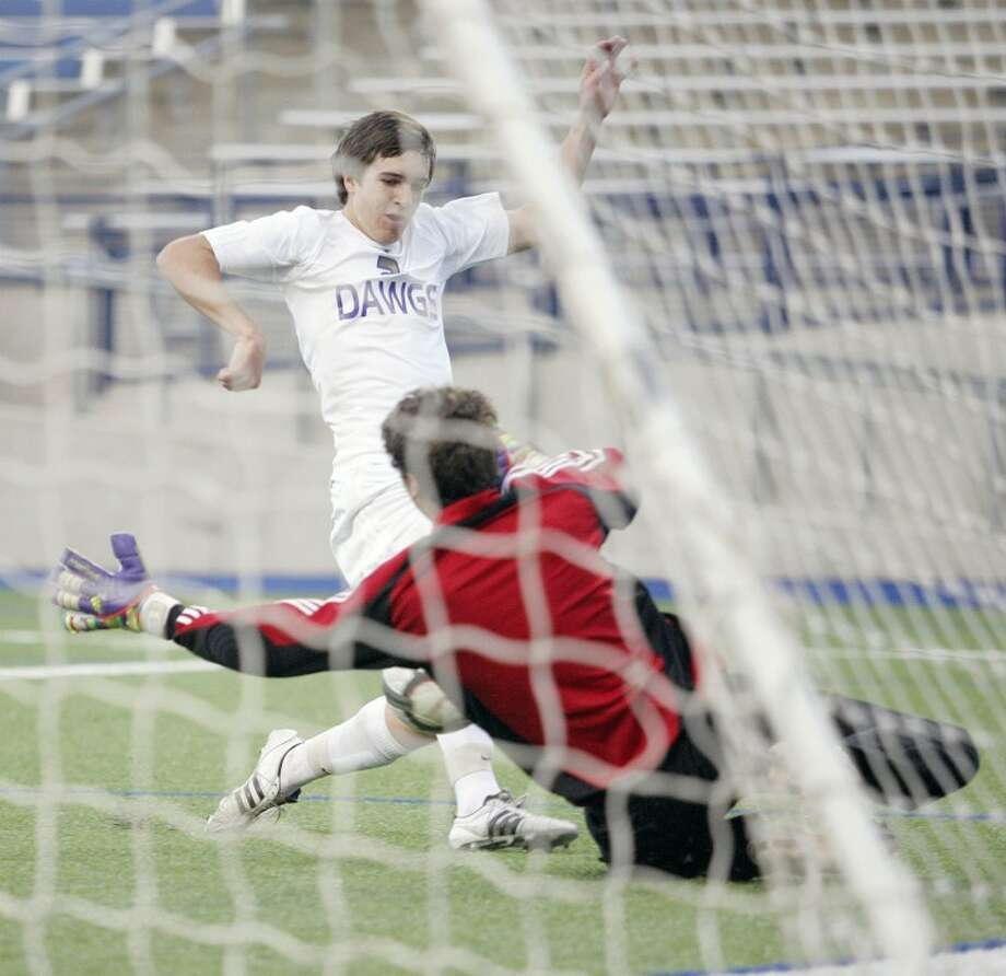 Midland High's John Durrett (2) scores against Abilene goalie Nathan Crow on Tuesday during their game at Grande Communications Stadium. Photo: Cindeka Nealy