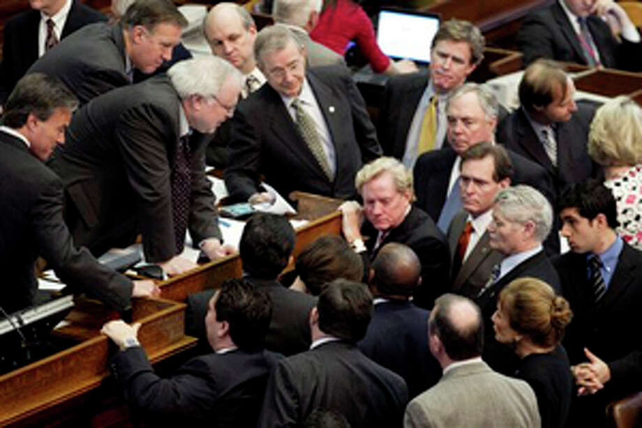 FILE - Texas state representatives gather around House Parliamentarian Chris Griesel, third from left, leaning over the dais, during debate of House Bill 1 in the House Chamber at the Capitol in Austin, Texas, on Sunday April 3, 2011. After completing the most contentious issues of education and health care for the needy Texans late Friday, the chamber turned to consideration of highways, prisons, state parks and dozens of other programs falling under the budget ax. The budget proposal spends $164.5 billion over the next two years in state and federal dollars. That's about $23 billion less than what is in the current budget. GOP leaders, in firm control of the Legislature, are vowing to balance the budget without raising new taxes. (AP Photo/Austin American-Statesman, Jay Janner) Photo: Jay Janner / Austin American-Statesman