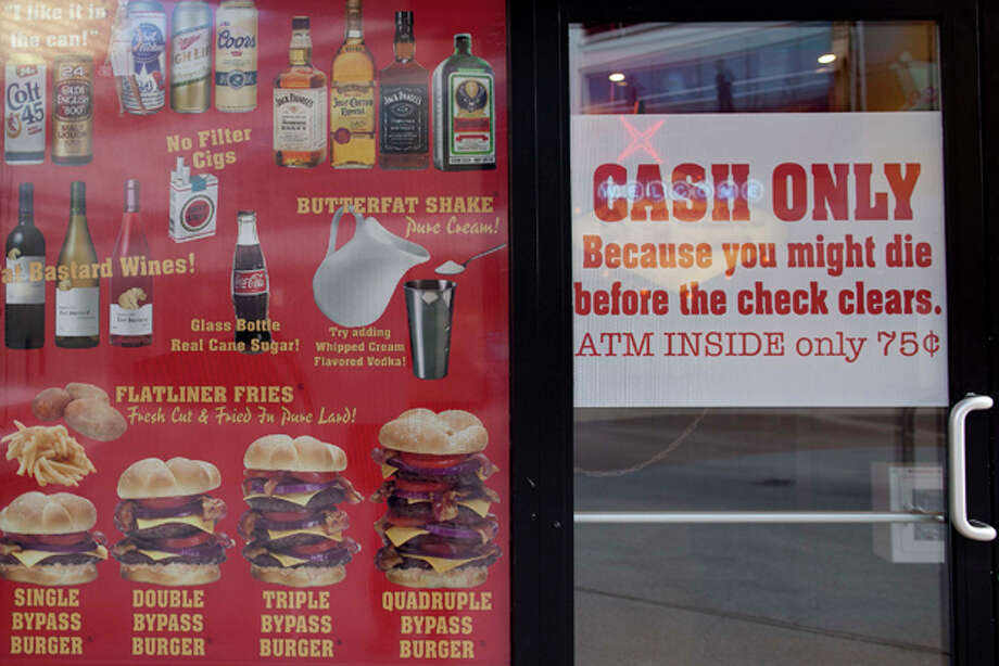 "Menu offerings and warnings are posted in the window of the Heart Attack Grill on Fremont Street, Wednesday, Feb. 15, 2012, in Las Vegas. The warnings nearly proved true for a man who was eating at the downtown Las Vegas restaurant that offers ""Bypass"" burgers, ""Flatliner "" fries and free meals to people over 350 pounds. A man was wheeled out of the restaurant on a stretcher Saturday evening, Feb. 11, 2011 after a medical episode that restaurant employees say looked like a heart attack. A Las Vegas fire spokesman tells The Associated Press paramedics were summoned Saturday evening and a man was indeed hospitalized. (AP Photo/Julie Jacobson) Photo: Julie Jacobson / AP"