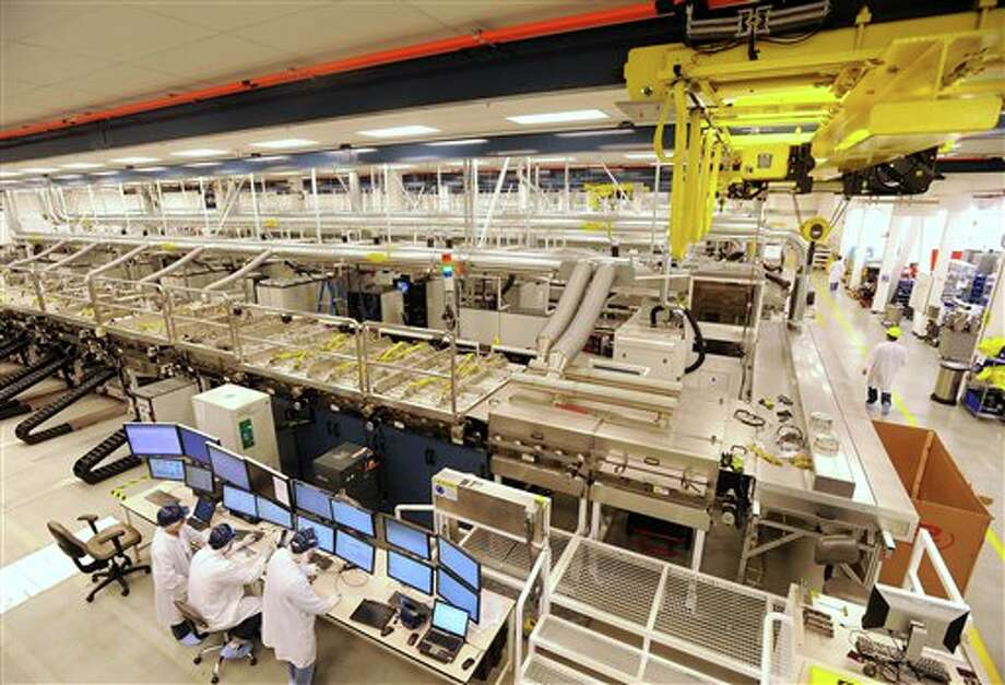 FILE - In this Oct. 6, 2010 file photo, workers monitor a control bank at Solyndra's solar panel factory on in Fremont, Calif. Homeowners on the hunt for sparkling solar panels are lured by ads filled with images of pristine landscapes and bright sunshine, and words about the technology's benefits for the environment _ and the wallet. What customers may not know is that there's a dirtier side. While solar is a far less polluting energy source than coal, many panel makers are nevertheless grappling with a hazardous waste problem. Fueled partly by billions in government incentives, the industry is creating millions of solar panels each year and, in the process, millions of pounds of polluted sludge and contaminated water. (AP Photo/Noah Berger, File) Photo: Noah Berger / AP2010