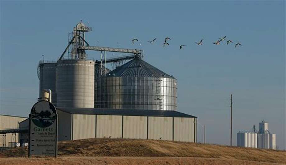 In this Feb. 5, 2013 photo geese fly by the East Kansas Agri-Energy ethanol plant in Garnett, Kan. that suspended production last year. Corn growers had high hopes going into the 2012 planting season but the drought that began last spring hit the corn crop hard. As a result, corn prices skyrocketed and corn has become scarce in some regions, forcing 20 ethanol plants around the country to halt production. Most are not expected to resume production until after 2013 corn is harvested in late August or September. (AP Photo/Orlin Wagner) Photo: Orlin Wagner / AP