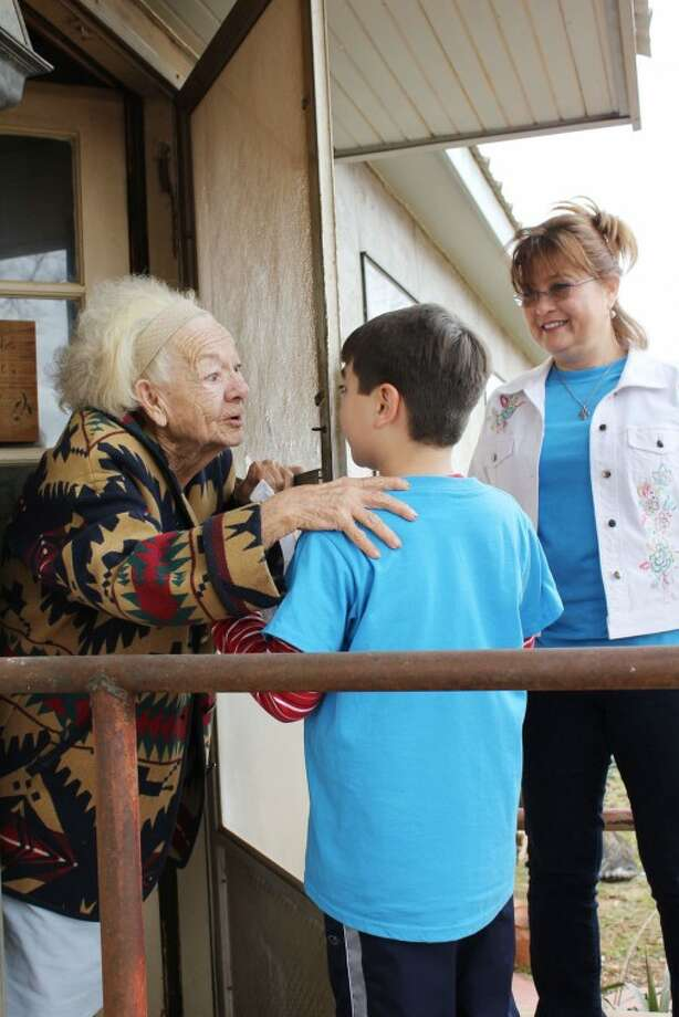Meals on Wheels client Tammye Conner talks with Bynum School student Evan McKinney Thursday morning during a Meals on Wheels delivery. A retired teacher, Conner said she loves visiting with the students. Photo: Meredith Moriak/Reporter-Telegram