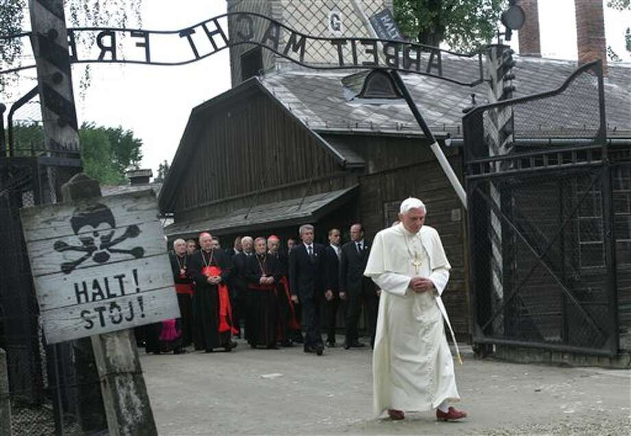"FILE - In this May 28, 2006 file photo, Pope Benedict XVI walks through the gate of the former Nazi concentration camp Auschwitz in Oswiecim, Poland, to pay his respects to the Holocaust victims. Sign at left reads ""stop"" in German and Polish. Sign above the gate reads ""Arbeit macht frei,"" German for ""work will set you free."" Declaring that he lacks the strength to do his job, Benedict announced Monday Feb. 11, 2013, he will resign Feb. 28 _ becoming the first pontiff to step down in 600 years. (AP Photo/Diether Endlicher) Photo: DIETHER ENDLICHER / AP"
