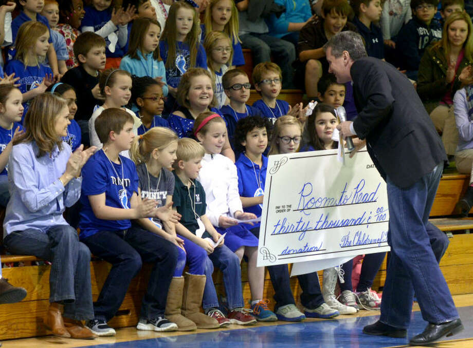 Room to Read founder John Wood accepts a check for $30,000 from Trinity School students Thursday in the school gym. The students raised the money through their Walk-a-thon fundraiser and were informed by Wood that the money would be used to fund a library in Nepal. James Durbin/Reporter-Telegram Photo: JAMES DURBIN