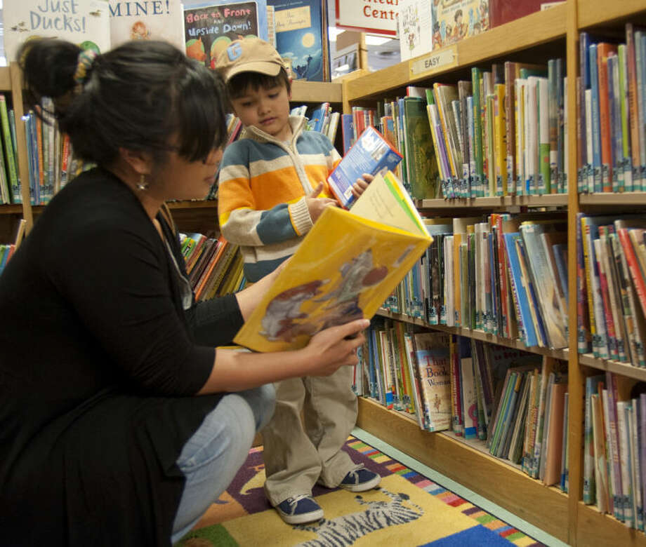 JoAnn Miller and her son J.D., 6, look at books to check out Monday at the Centennial Branch of the Midland County Library. Miller said they are excited for the opening of the new library off Loop 250. Tim Fischer\Reporter-Telegram Photo: Tim Fischer