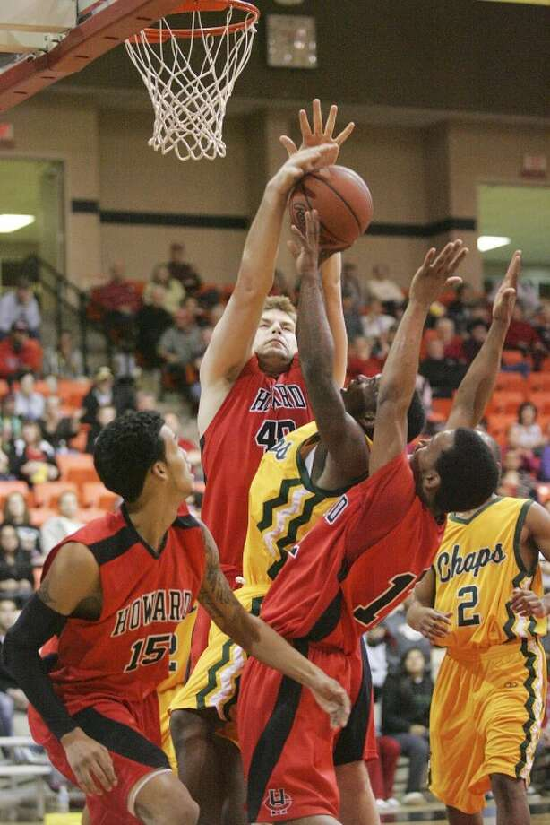 Midland College's Willis Nicholson (5) shot is blocked as he's guarded by Howard College's Jacob Thomas (15), Chad Posthumus (40) and Rico Richardson (12) Thursday during their game at Dorothy Garrett Coliseum in Big Spring. Cindeka Nealy/Reporter-Telegram Photo: Cindeka Nealy