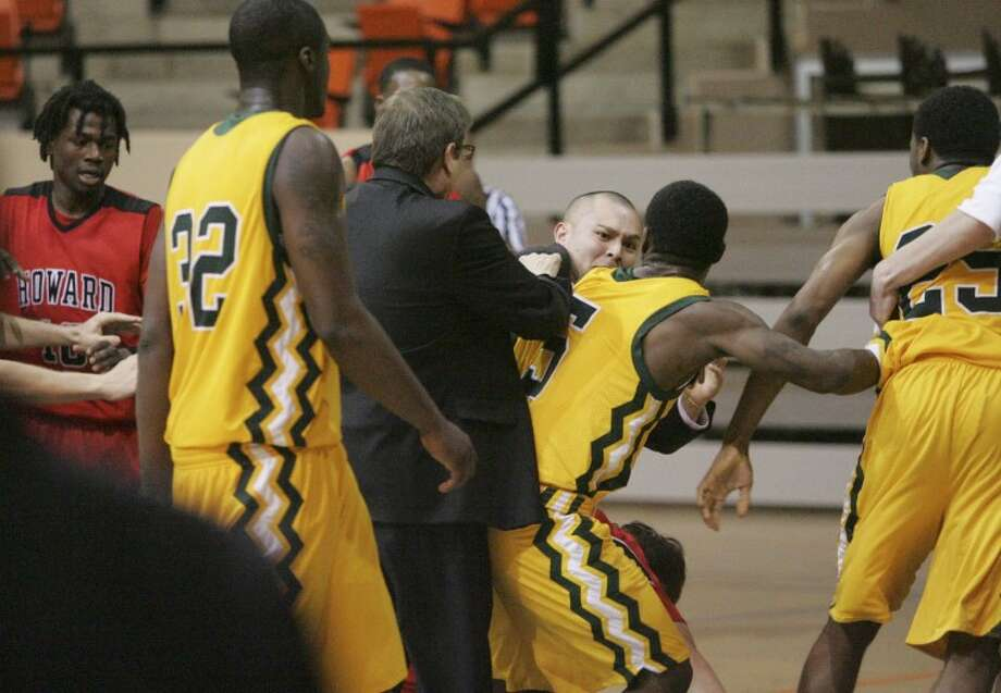 Howard College Asst. Coach Jase Coburn tries seperate the teams after a bench clearing fight broke out with a 1:13 seconds left in their game on Thursday at Dorothy Garrett Coliseum in Big Spring. Cindeka Nealy/Reporter-Telegram Photo: Cindeka Nealy