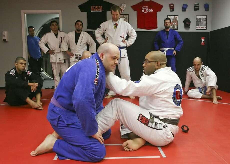 Brad Barns, left, sits in while Mixed Martial Arts Instructor Bruno Bastos demonstrates a submission move Saturday during Brazilian Jiu-Jitsu seminar at Rhino BJJ. Cindeka Nealy/Reporter-Telegram Photo: Cindeka Nealy