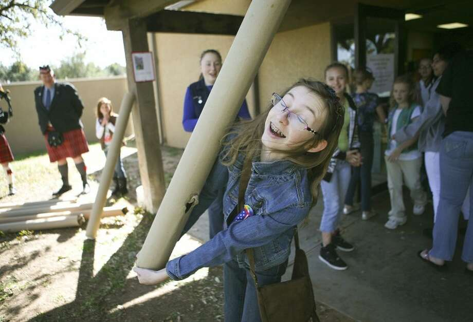 "Katie Curran, 13, prepares to launch a cardboard cylinder at the ""caber toss"" Monday during the annual Thinking Day event at the Girl Scouts of the Desert Southwest. The caber toss, which is a traditional Scottish athletic event practiced in Scotland, was one of several activities the girls scouts did to help them learn about the different countries and cultures of Girl Scouts from around the world. Cindeka Nealy/Reporter-Telegram Photo: Cindeka Nealy"