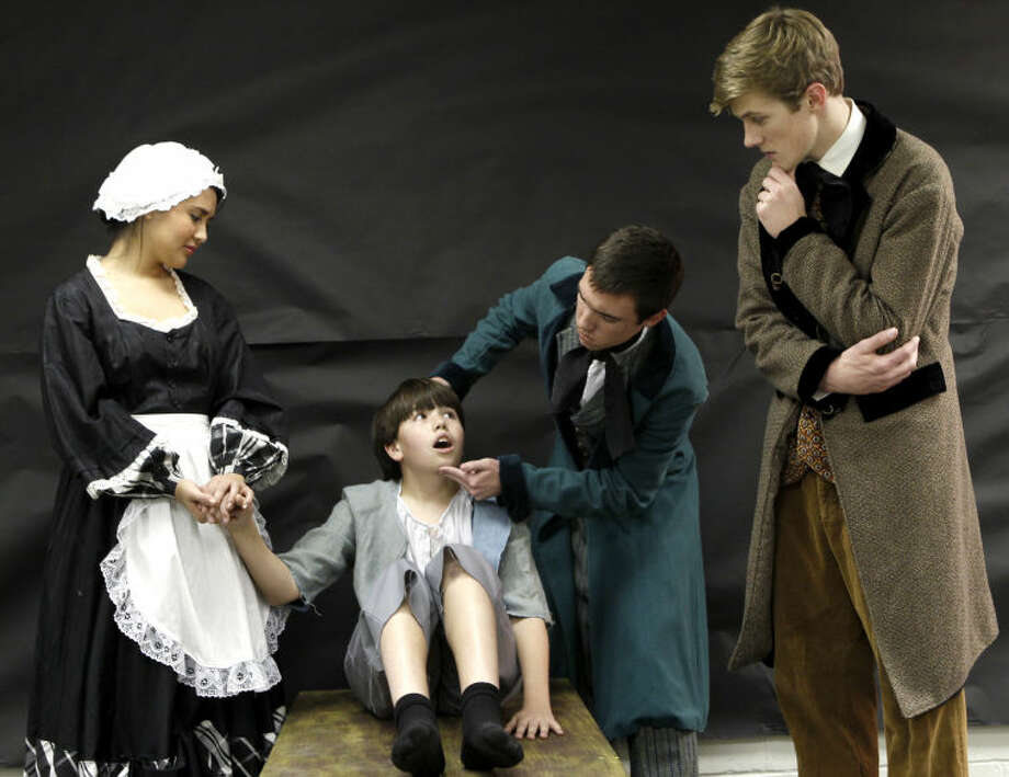 "From left, Zureyma Thompson as 'Mrs. Bedwin,' Jordan Sanz as 'Oliver,' Zack Lyon as 'Doctor Grimwig,' and Lewis Grimes as 'Mr. Brownlow' act out a scene from the musical ""Oliver"" during rehearsal Wednesday at Trinity School. James Durbin/Reporter-Telegram Photo: JAMES DURBIN"
