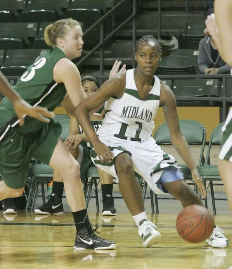 Midland College's Darnetta Jackson (11) drives in as she's guarded by Western Texas College's Jessica McCarville (13) Monday during their game at Chaparral Center. Cindeka Nealy/Reporter-Telegram Photo: Cindeka Nealy