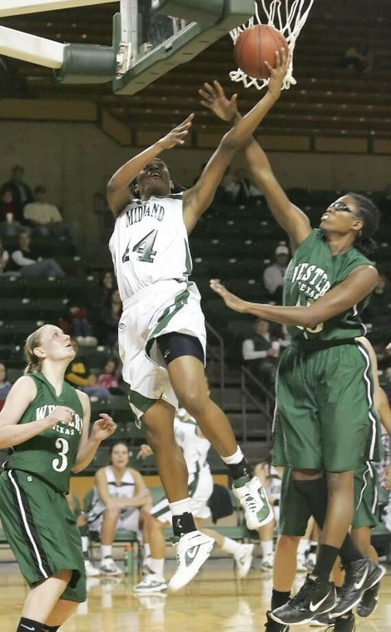 Midland College's Achiri Ade (44) goes to the air to attempt a layup as she guarded by Western Texas College's Presley Gann (3) and Shaylese Shofner (45) during their game at Chaparral Center last week. Cindeka Nealy/Reporter-Telegram Photo: Cindeka Nealy
