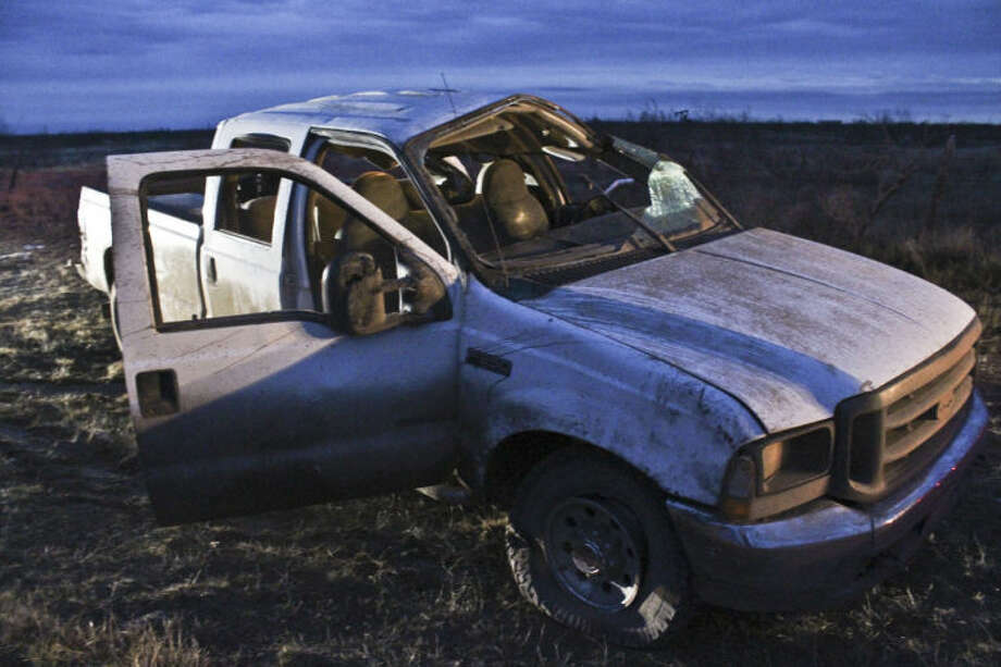 A white pickup rests in a ditch in south Midland County after its driver lost control in a rollover crash on Farm-to-Market Road 1787 Tuesday night. Tyler White/Reporter-Telegram Photo: Tyler White