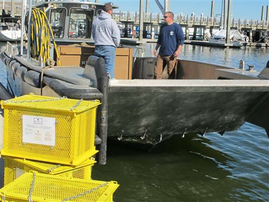 Bottles of Cabernet Sauvignon in protective steel cages, left, are ready to be loaded onto a boat in Charleston, S.C., on Wednesday, Feb. 20, 2013. Mira Winery of St. Helena, California, submerged four cases of wine in Charleston Harbor on Wednesday to see what effect the ocean has on aging the wine. Similar experiments with ocean aging have been conducted in Europe. (AP Photo/Bruce Smith) Photo: Bruce Smith / AP