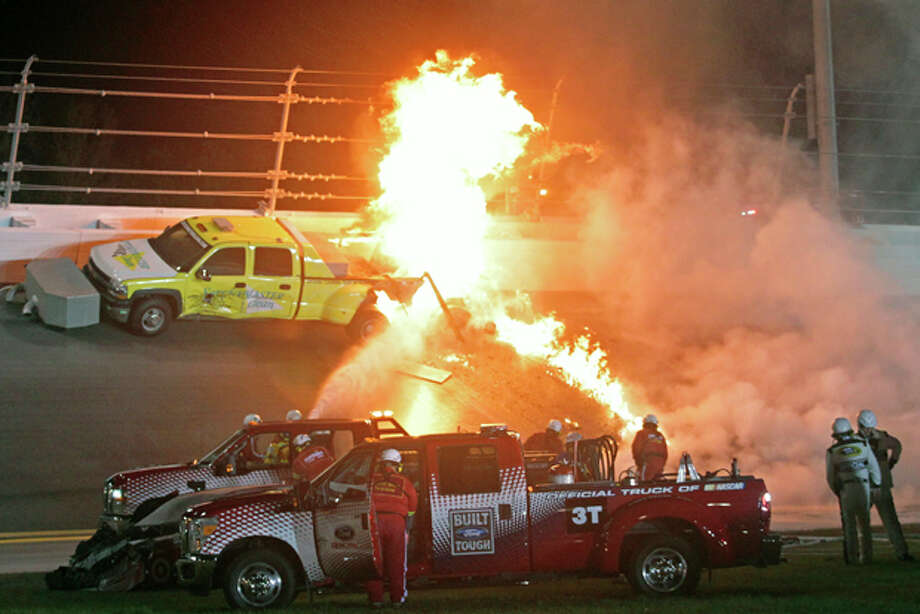 Emergency workers try to put out a fire after Juan Pablo Montoya's car struck the truck during the NASCAR Daytona 500 auto race at Daytona International Speedway in Daytona Beach, Fla., Monday, Feb. 27, 2012. (AP Photo/Bill Friel) Photo: Bill Friel / FR45172 AP