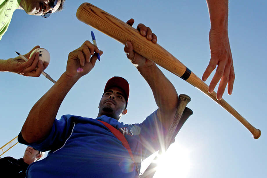 Texas Rangers right fielder Nelson Cruz signs autographs during baseball spring training, Sunday, Feb. 26, 2012, in Surprise, Ariz. (AP Photo/Charlie Riedel) Photo: Charlie Riedel / AP