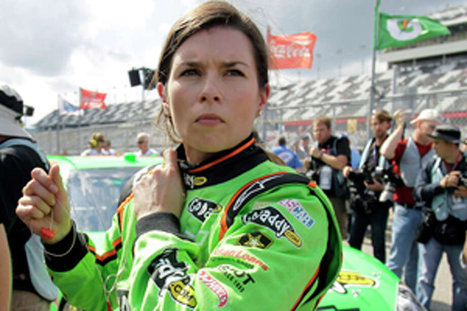 Danica Patrick removes her earplugs as she stands by he car after her qualifying run for the NASCAR Daytona 500 auto race at Daytona International Speedway, Sunday, Feb. 19, 2012, in Daytona Beach, Fla. (AP Photo/John Raoux) Photo: John Raoux / AP