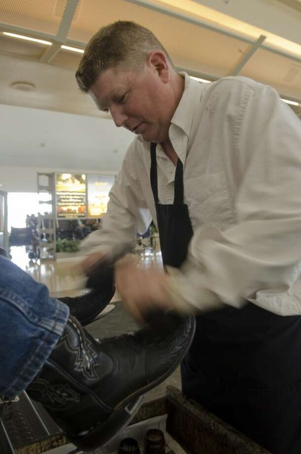 Josh Manuel shines a pair of boots Friday at his Immanuel Shine inside Midland International Airport. Photo by Tim Fischer/Midland Reporter-Telegram Photo: Tim Fischer