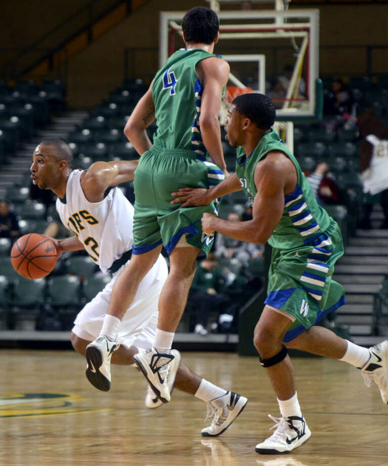 Midland College's Corey Hilliard sidesteps a block from Western Texas' Austin Shockley and Justin Roberson Monday at Chaparral Center. James Durbin/Reporter-Telegram Photo: JAMES DURBIN