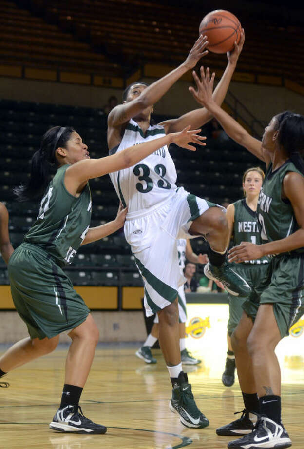 (File Photo) Midland College's Achiri Ade attempts a layup against Western Texas' Jacoree Brooks and Brianna Sifford Monday at Chaparral Center. James Durbin/Reporter-Telegram Photo: JAMES DURBIN