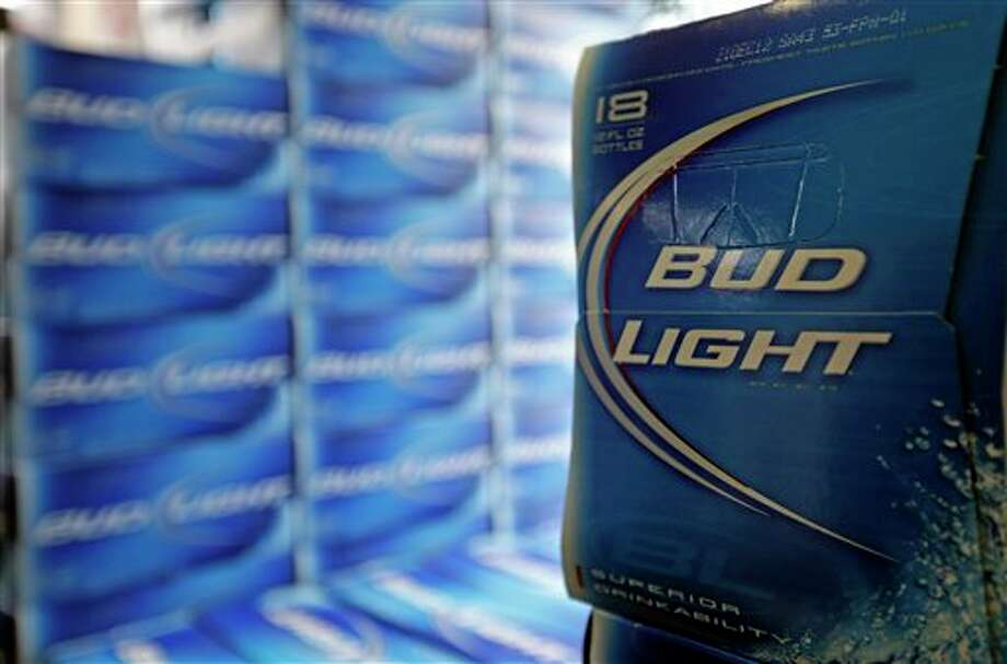 FILE - In this Monday, Jan. 28, 2013, file photo, Bud Light beer is shown in the aisles of Elite Beverages in Indianapolis. Beer lovers across the country have filed $5 million class-action lawsuits accusing Anheuser-Busch of watering down its Budweiser, Michelob and other brands. (AP Photo/Michael Conroy, File) Photo: Michael Conroy / AP