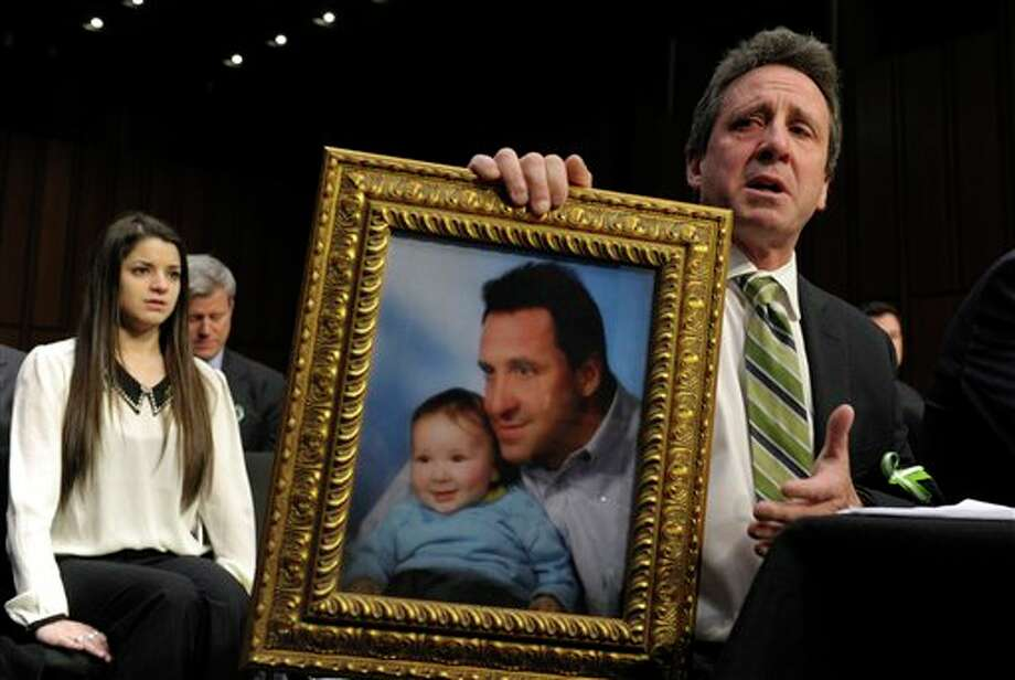 Neil Heslin, the father of a six-year-old boy who was slain in the Sandy Hook massacre in Newtown, Conn., on Dec. 14, holds a picture of himself with his son Jesse and wipes his eye while testifying on Capitol Hill in Washington, Wednesday, Feb. 27, 2013, before the Senate Judiciary Committee on the Assault Weapons Ban of 2013. At left is Carlee Soto, sister of slain Sandy Hook Elementary teacher Victoria Soto. (AP Photo/Susan Walsh) Photo: Susan Walsh / AP