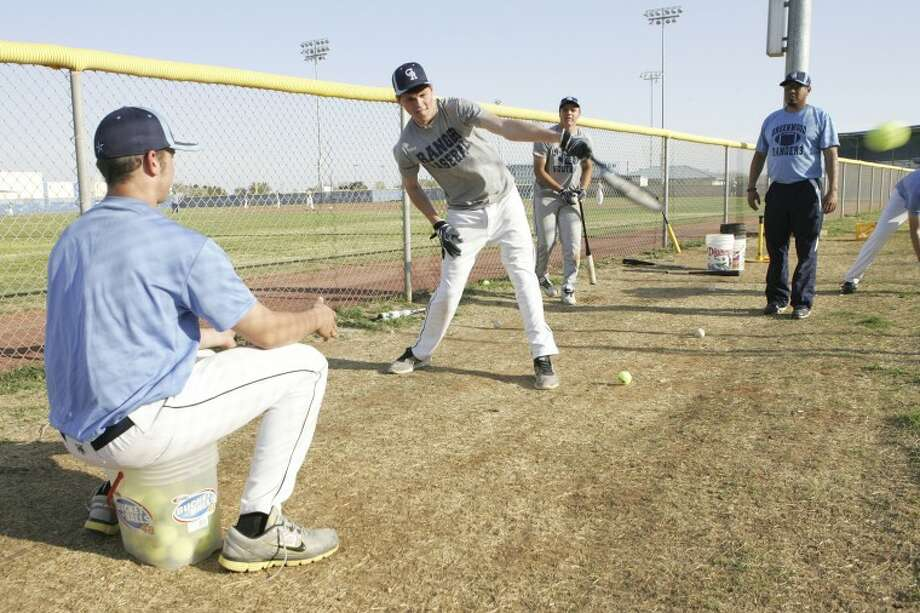 Asst. Coach Steven Rodriguez watch as Call Carmichael, left, pitches Cade Jones the ball, during a swinging technique drill, Wednesday at the Greenwood High School baseball field. Cindeka Nealy/Reporter-Telegram Photo: Cindeka Nealy