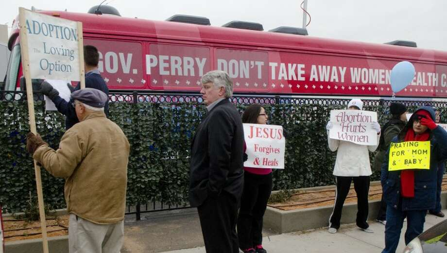 Anti-abortion protesters carry signs and watch outside Planned Parenthood Thursday as supporters rally inside to protest funding cuts to women's health. Photo: Tim Fischer/Reporter-Telegram