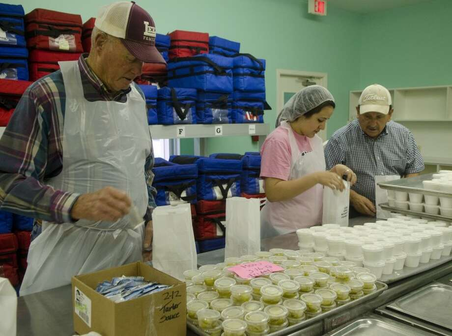 Ernie Johnson, Bryanna Rendon and Luis Galan place items in sack lunches Friday at Meals-on-Wheels. Photo: Tim Fischer/Reporter-Telegram