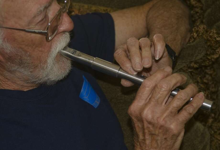 Clint Adams demonstrates the tunes of an Irish whistle. Photo: Tim Fischer/Reporter-Telegram