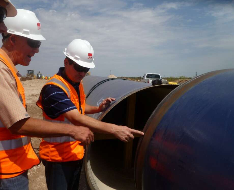 Mayor Wes Perry and Jay Edwards, general manager for Midland County Freshwater District #1, look over a section of the pipe that will carry water and how the pipe will ft together during a tour pipeline construction in Ector County Thursday afternoon. Photo by Kathleen Petty
