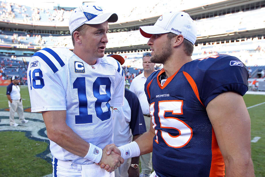 FILE - In this Sept. 26, 2010 file photo, Indianapolis Colts quarterback Peyton Manning (18) greets Denver Broncos quarterback Tim Tebow (15) at an NFL game, in Denver. Manning is negotiating to join the Broncos, ESPN reported Monday, March 19, 2012. Citing anonymous sources, ESPN said that the four-time MVP has instructed agent Tom Condon to negotiate the details of a deal with Denver. (AP Photo/Greg Trott) Photo: Greg Trott / AP2010