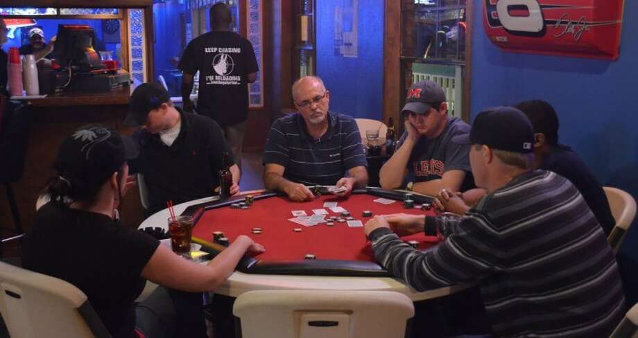 An intense game of poker between several players during the second round of Friday's night poker tournament at Woofers and Tweeter's. Photo: James Cannon/MRT