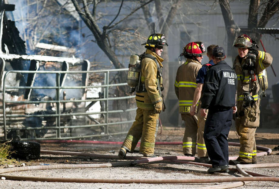 Midland firefighters work the scene of a trailer fire near South Dallas Street and East Hicks Avenue on Tuesday. James Durbin/Reporter-Telegram Photo: JAMES DURBIN