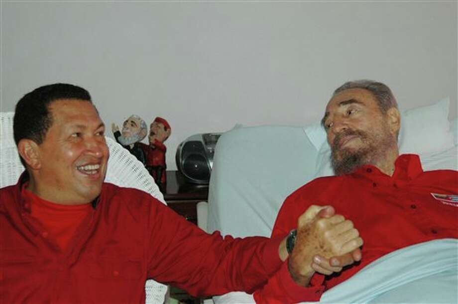 FILE - In this Aug. 13, 2006 file photo released by Cuba's Communist daily newspaper Granma, Cuba's leader Fidel Castro, right, and Venezuela's President Hugo Chavez hold hands as Castro recuperates from surgery in Havana, Cuba. Venezuela's Vice President Nicolas Maduro announced on Tuesday, March 5, 2013 that Chavez has died at age 58 after a nearly two-year bout with cancer. (AP Photo/Granma, File) Photo: HOPD / GRANMA