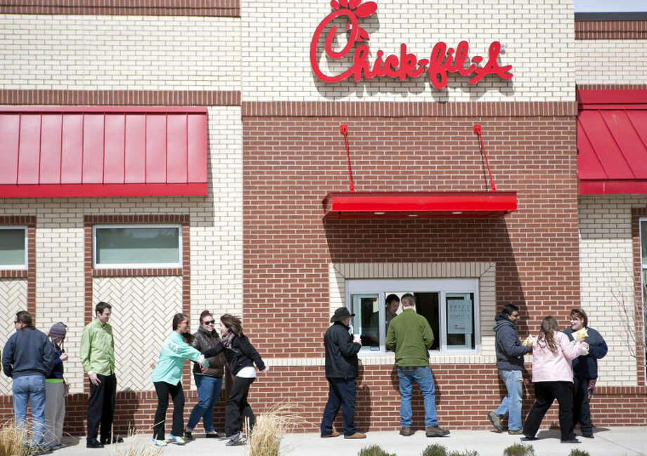 "(File Photo) Participants walk past the drive-through window to collect a free lunch during the ""First 100"" event Wednesday, March 6 at the new Chick-Fil-A location at the intersection of Wall Street and Andrews Highway in Midland. The first 100 people in line when the doors open at 6 a.m. on Thursday, March 7, will win a one-year supply of Chick-Fil-A meals. James Durbin/Reporter-Telegram Photo: JAMES DURBIN"