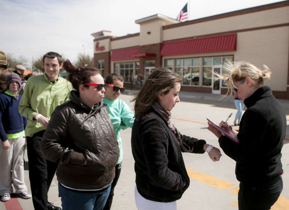 "Kim Pharaoh (right) of the Chick-Fil-A marketing team checks Erin Fehrenbach's wristband as she stands in line during the ""First 100"" event Wednesday, March 6 at the new Chick-Fil-A location at the intersection of Wall Street and Andrews Highway in Midland. The first 100 people in line when the doors open at 6 a.m. on Thursday, March 7, will win a one-year supply of Chick-Fil-A meals. James Durbin/Reporter-Telegram Photo: JAMES DURBIN"