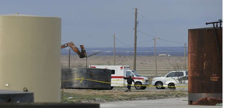 Desert Tanks employees remove a steel oil tank lid from the scene where human remains were discovered near the Big Spring airport Tuesday, March 20, 2012. Officials used the large tank lid to preserve the scene overnight until FBI evidence recovery personnel could arrive to process the scene. (AP Photo/The Abilene Reporter-News,Greg Kendall-Ball ) Photo: Greg Kendall-Ball
