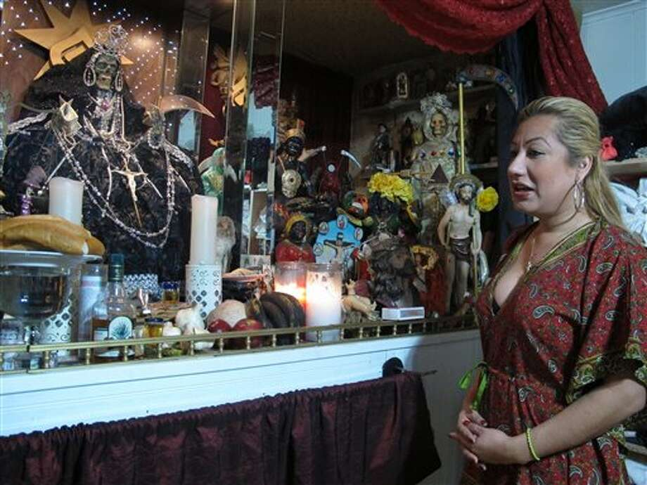 In this Feb. 12, 2013 photo, Arely Vazquez Gonzalez, a Mexican immigrant and transgender woman, is shown with her alter to La Sante Muerte at her Queens, NY apartment. La Santa Muerte, an underworld saint most recently associated with the violent drug trade in Mexico, now is spreading throughout the U.S. among a new group of followers ranging from immigrant small business owners to artists and gay activists. (AP Photo/Russell Contreras) Photo: Russell Contreras / AP