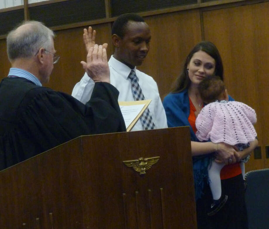 Meddie Mugoya raises his right hand and takes the oath administered by Judge Robert Junell Friday to become an American citizen. Mugoya, a native of Uganda, now calls Midland home with his wife Sarah and their three children. The couple have also started the Africa Bridges of Hope Ministry in 2006 to support Ugandan children. Photo by Audrie Palmer