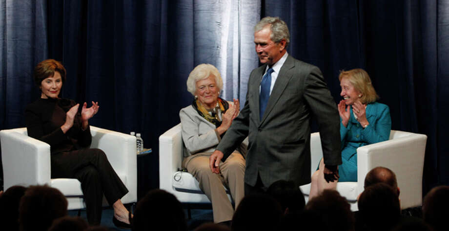 "President George W. Bush, front, walks back to his seat after introducing First Ladies Laura Bush, left, and Barbara Bush, second from left, with moderator Doris Kearns Goodwin during a panel that was part of the conference ""America's First Ladies: An Enduring Vision,"" at SMU in Dallas, Monday, March 5, 2012. (AP Photo/LM Otero) Photo: LM Otero / AP"