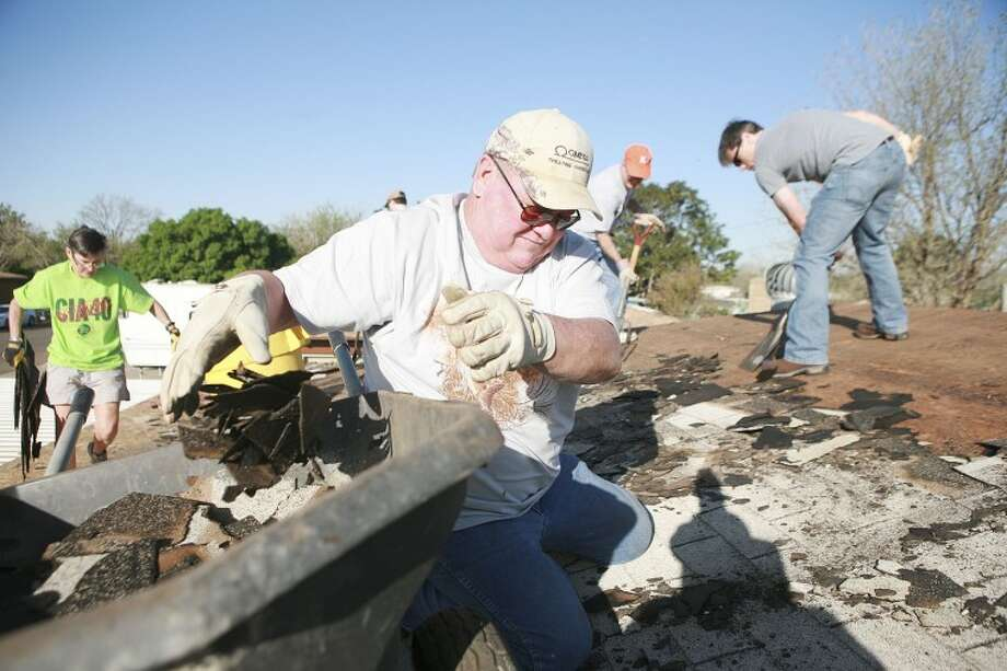 Christmas in Acton volunteer Craig Beeson tosses old shingles into a wheelbarrow as members of Crestview Baptist Church prepare to replace the roof shingles, Saturday at 3303 W. Kansas Ave. Cindeka Nealy/Reporter-Telegram Photo: Cindeka Nealy