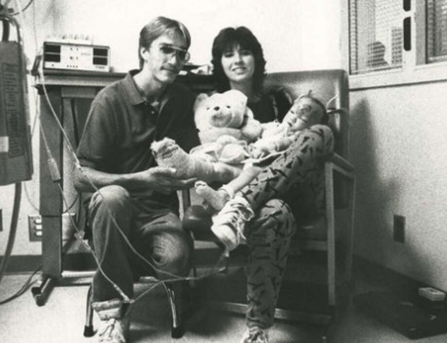 "Chip and Reba McClure sit with daughter Jessica and a teddy bear she receive from vice president George Bush at Midland Memorial Hospital where Jessica was recovering after her rescue from her ordeal. (""Baby Jessica"" Rescue File - Oct. 18, 1987"