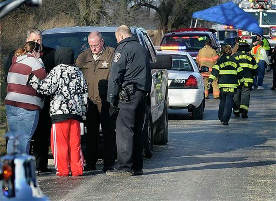 Will County Sheriff's officials and a Wilmington Police officer inform women waiting at the scene near Wilmington, Ill., that the bodies of four teenagers were in a car discovered submerged in Forked Creek on Tuesday morning March 12, 2013. Two boys and two girls, aged 15 to 17, apparently skidded off a bridge into the icy creek. Authorities say the teens had been missing since Monday evening and don't know exactly when the accident occurred. (AP Photo/Daily Journal, Mike Voss) Photo: Mike Voss / The Daily Journal