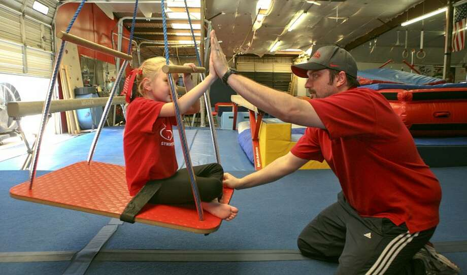 After spinning and pushing Sarah Bruehl, 6, on a swing, Big Fun Coach Matt Koffel asks her to watch and touch his hands during a hand and eye coordination drill March 23, at Next Level Gymnastics. Koffel is helping Bruehl, who suffered a stage three intraventricular brain hemorrhage at four days old, learn the simple movements that come natural to other children her age. Cindeka Nealy/Reporter-Telegram Photo: Cindeka Nealy