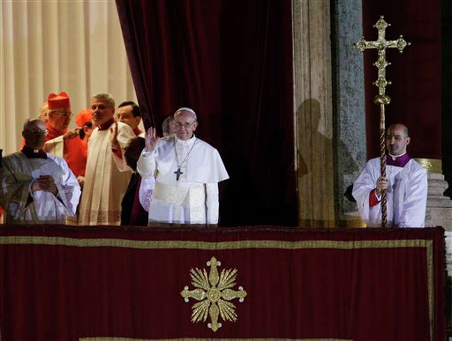 Pope Francis flanked by Monsignor Guido Marini, master of liturgical ceremonies, waves to the crowd from the central balcony of St. Peter's Basilica at the Vatican, Wednesday, March 13, 2013. Cardinal Jorge Bergoglio, who chose the name of Francis is the 266th pontiff of the Roman Catholic Church. (AP Photo/Andrew Medichini) Photo: Andrew Medichini / AP2013