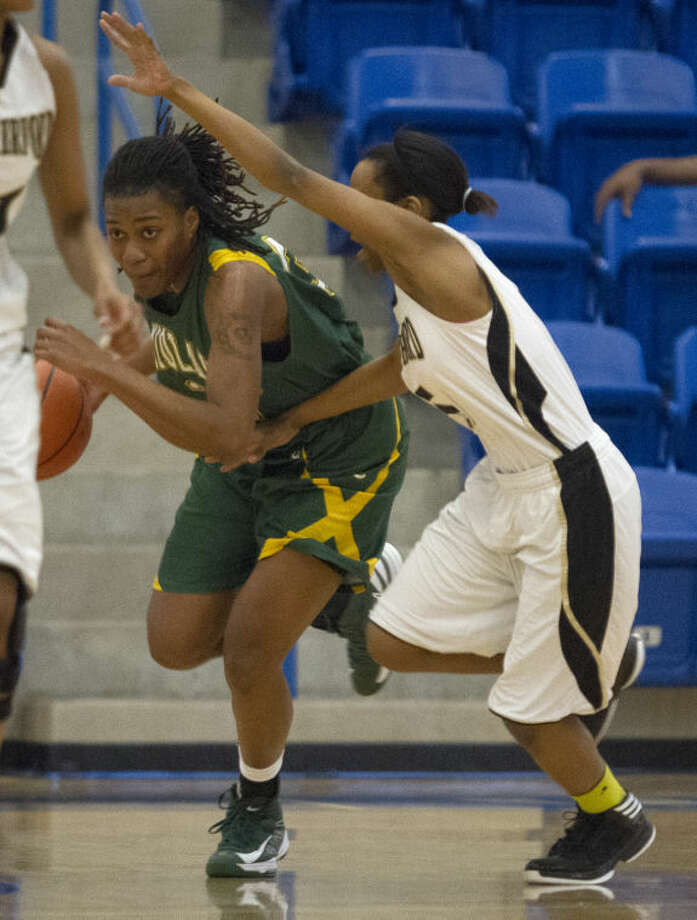 Midland College forward Achiri Ade tries to push past Weatherford College guard Bre Brooks during the Lady Chaparrals' game against the Lady Coyotes on Saturday in the Rip Griffin Center in Lubbock. Photo: Brad Tollefson